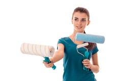 Młody rozochocony brunetki kobiety budowniczy w mundurze z farba rolownikiem w rękach robi reovations odizolowywającym na białym  Zdjęcia Stock