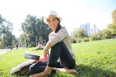 Młody rozochocony kobiety czytelniczej książki obsiadanie w centrala parku zdjęcia stock