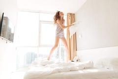 Młody rozochocony kobiety doskakiwanie na łóżku i bawić się z poduszką Zdjęcie Royalty Free