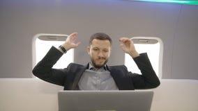 Młody rozochocony prawnika biznesmen pracuje z laptopem, mieć zabawę w samolotowym wnętrzu przedsiębiorcy samolot zdjęcie wideo