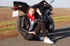 Młody rozważny dziewczyna rowerzysta w eleganckich ubraniach, plenerową podróż z rowerem, wp8lywy przerwa, siedzi na asfalcie, do obraz stock