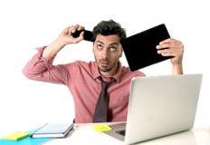 Młody ruchliwie biznesmen patrzeje szalony desperackiego przy biurowym biurkiem pracuje z telefon komórkowy cyfrową pastylką i ko Fotografia Stock