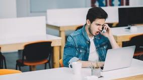 Młody ruchliwie mężczyzna z brodą pracuje na laptopie i używa telefon komórkowego fotografia stock