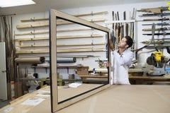 Młody rzemieślnik koncentruje na robić obrazek ramie w warsztacie Obrazy Royalty Free