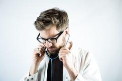Młody samiec lekarki kładzenie na stetoskopie fotografia royalty free