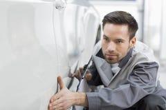 Młody samochodu mechanik egzamininuje samochód w remontowym sklepie obraz royalty free