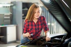 Młody seksowny brunetka mechanik w sprawdzać koszula w garażu Obrazy Stock