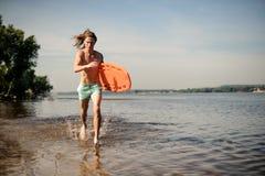 Młody seksowny długowłosy plażowy ratownika bieg w wodzie z lif Obrazy Royalty Free