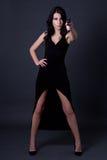 Młody seksowny kobieta tajny agent w czerni smokingowy pozować z armatnim ove Obrazy Stock