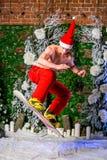 Młody seksowny sporty młody człowiek w czerwieni spodniach i Santa kapeluszowy doskakiwanie z snowboard zdjęcia royalty free
