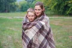 Młody siostry i brata stojak zakrywający z szkocką kratą w parku Obraz Stock