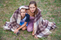 Młody siostry i brata stojak zakrywający z szkocką kratą w parku Obrazy Stock