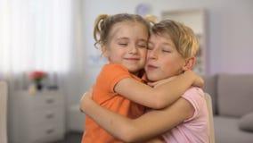 Młody siostrzany przytulenie brata rysunek przy stołem, całowanie policzki each inny, miłość zbiory