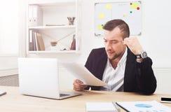 Młody skoncentrowany biznesmen czyta dokumenty w nowożytnym białym biurze obrazy royalty free