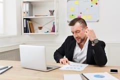 Młody skoncentrowany biznesmen czyta dokumenty w nowożytnym białym biurze obrazy stock