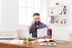 Młody skoncentrowany biznesmen czyta dokumenty w nowożytnym białym biurze zdjęcia stock