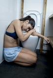 Młody smutnej i przygnębionej bulimic kobiety czuciowy chory obsiadanie przy podłoga toaleta opiera na WC Zdjęcia Stock