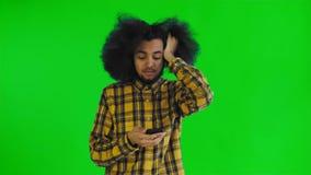 Młody smutny amerykanina mężczyzna używa telefon i dostawać złą wiadomość na zieleń ekranie lub chroma kluczowym tle Poj?cie zbiory