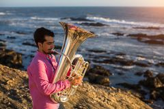 Młody smutny muzyk bawić się trąbkę na oceanu wybrzeżu Fotografia Stock