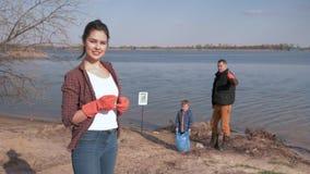 Młody społeczeństwo przeciw zanieczyszczeniu, portret uśmiechnięty kobieta wolontariusz daje kciukowi na w górę unfocused tła rod zbiory