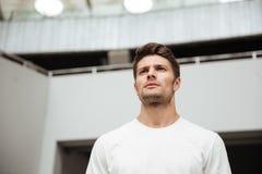 Młody sporta mężczyzna stoi blisko popielatej ściany outdoors zdjęcie royalty free