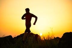 Młody sportowa bieg na Skalistym Halnym śladzie przy zmierzchem aktywny tryb życia zdjęcia royalty free