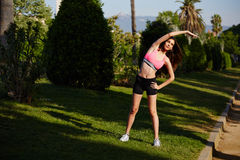Młody sportowy żeński biegacz robi rozciągania exer Obraz Stock