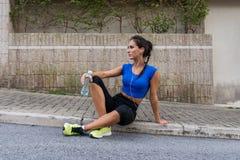 Młody sportowy żeński odpoczywać ćwiczy, słuchający muzyka w słuchawkach, trzyma butelkę woda po tym jak działający zdjęcie stock