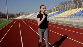 Młody sportowy atrakcyjny dysponowany kobieta bieg jogging w zwolnionym tempie, plenerowy duży stadium trening na pogodnym wiosna zbiory