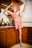 Młody sportowy, elastyczny przy kuchenką, szpilki kobiety blondynki dziewczyna kosztuje polewkę z miarką lub kopyścią Obrazy Royalty Free