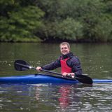 Młody sportowy mężczyzna siedzi w sporta kajaka łódkowaty ono uśmiecha się na szerokim zdjęcia stock