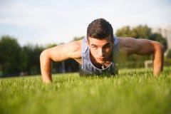 Młody sportowy mężczyzna szkolenie i robić prasa podnosimy outdoors zdjęcia stock