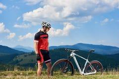 Młody sportowy sportowa rowerzysta patrzeje mtb na halnym trawiastym wzgórzu w fachowym sportswear obrazy stock