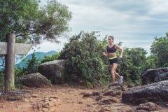 Młody sportsmenka przecinającego kraju bieg na brudnym skalistym footpath w górach w lecie Dysponowana dziewczyna jogging outdoor fotografia stock