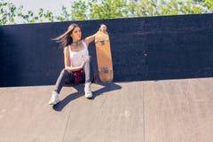 M?ody sporty dziewczyny mienia deskorolka Outdoors, miastowy styl ?ycia zdjęcia royalty free