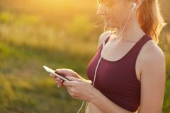 Młody sporty kobieta bieg, robić sportowi, będący ubranym wierzchołek, słuchający muzyka z słuchawkami i telefonem komórkowym, ci obraz stock