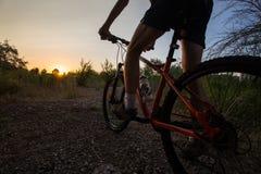 Młody sporty mężczyzna jedzie bicykl przy zmierzchem Obrazy Royalty Free