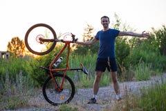 Młody sporty mężczyzna trzyma bicykl przy zmierzchem Obrazy Stock