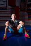 Młody sporty męski bokser siedzi w miarowym boxi w bokserskich rękawiczkach Zdjęcia Royalty Free