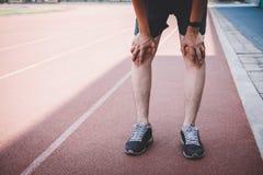Młody sprawności fizycznej atlety mężczyzna odpoczynek podczas i męczy na droga śladzie, ćwiczenie treningu wellness pojęcie zdjęcie royalty free