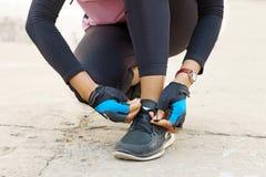 Młody sprawności fizycznej kobiety biegacz wiąże shoelace Zdjęcia Royalty Free