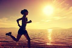 Młody sprawności fizycznej kobiety biegacza bieg na wschodu słońca nadmorski Fotografia Stock