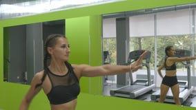 Młody sprawności fizycznej kobiety szkolenie przed lustrem przy gym Żeńska atleta rozciąga jej ręki i ciało przedtem Fotografia Royalty Free