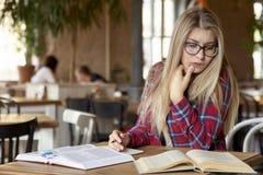 Młody studencki kobiety obsiadanie przy stołem w kawiarni przy uniwersytetem zdjęcia royalty free