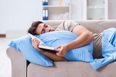 Młody studencki mężczyzna narządzanie dla szkoła wyższa egzaminów w łóżku z książką Fotografia Stock