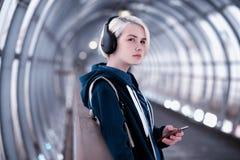 Młody studencki słuchanie muzyka w dużych hełmofonach w metrze obrazy stock