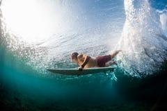 Młody surfingowiec nurkuje pod ocean fala obrazy stock