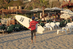 Młody surfingowiec trzyma kipieli deski na Herzliya plaży, Izrael Zdjęcia Stock