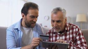 Młody syn i przechodzić na emeryturę ojciec wkłada numer karty kredytowej na zakładce, płatniczy app zbiory