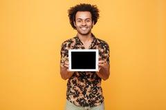 Młody szczęśliwy afro amerykański mężczyzna pokazuje pustego ekranu komputeru osobistego pastylkę Zdjęcia Royalty Free